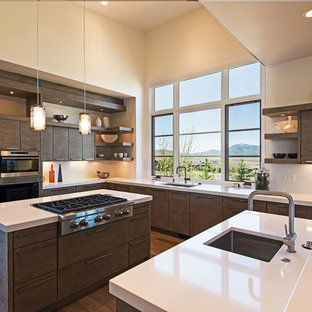 Example of a trendy u-shaped dark wood floor kitchen design in Salt Lake City with an undermount sink, flat-panel cabinets, dark wood cabinets, stainless steel appliances and an island