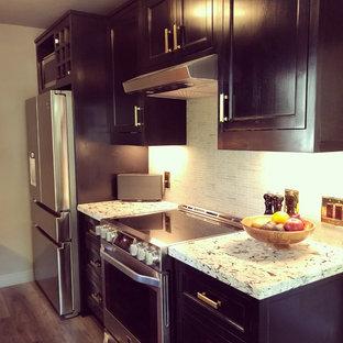 На фото: маленькая параллельная кухня в стиле фьюжн с обеденным столом, врезной раковиной, фасадами в стиле шейкер, черными фасадами, столешницей из кварцита, бежевым фартуком, фартуком из известняка, техникой из нержавеющей стали, полом из линолеума, коричневым полом и белой столешницей с