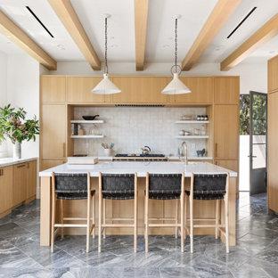 ロサンゼルスの広いトランジショナルスタイルのおしゃれなキッチン (アンダーカウンターシンク、フラットパネル扉のキャビネット、淡色木目調キャビネット、大理石カウンター、白いキッチンパネル、モザイクタイルのキッチンパネル、パネルと同色の調理設備、大理石の床、黒い床、白いキッチンカウンター、表し梁) の写真