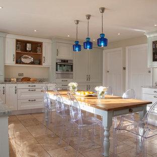 Exemple d'une cuisine américaine nature en L avec un placard avec porte à panneau encastré, des portes de placard bleues, une crédence beige, un électroménager noir, un sol en travertin et aucun îlot.