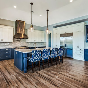 Inspiration for a large transitional l-shaped open plan kitchen in Tampa with a farmhouse sink, shaker cabinets, white cabinets, recycled glass benchtops, multi-coloured splashback, porcelain splashback, stainless steel appliances, porcelain floors and with island.