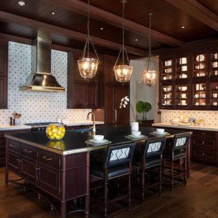 Idéer för ett stort exotiskt svart kök, med en undermonterad diskho, skåp i shakerstil, skåp i mörkt trä, bänkskiva i kvartsit, flerfärgad stänkskydd, stänkskydd i keramik, svarta vitvaror, mörkt trägolv, en köksö och brunt golv