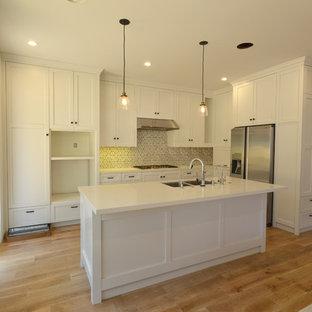 ロサンゼルスのトランジショナルスタイルのおしゃれなキッチン (ダブルシンク、シェーカースタイル扉のキャビネット、白いキャビネット、珪岩カウンター、白いキッチンパネル、セラミックタイルのキッチンパネル、シルバーの調理設備、淡色無垢フローリング) の写真