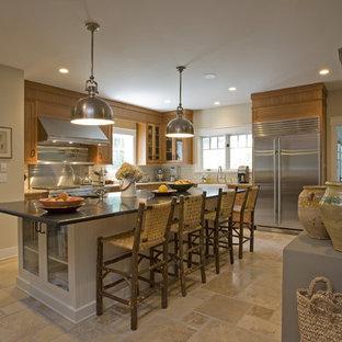 ニューヨークの広いラスティックスタイルのおしゃれなキッチン (シルバーの調理設備、エプロンフロントシンク、フラットパネル扉のキャビネット、中間色木目調キャビネット、御影石カウンター、白いキッチンパネル、サブウェイタイルのキッチンパネル、セラミックタイルの床) の写真
