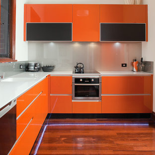 Photo of a mid-sized contemporary l-shaped kitchen pantry in Perth with an integrated sink, flat-panel cabinets, orange cabinets, solid surface benchtops, metallic splashback, glass sheet splashback, stainless steel appliances, dark hardwood floors and no island.