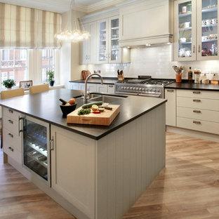 Klassische Küche in L-Form mit Doppelwaschbecken, Glasfronten, grauen Schränken, Küchenrückwand in Weiß, Rückwand aus Metrofliesen, Küchengeräten aus Edelstahl, hellem Holzboden und Kücheninsel in London