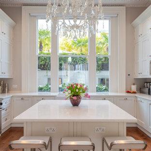 Exempel på ett stort klassiskt vit vitt u-kök, med en rustik diskho, skåp i shakerstil, vita skåp, glaspanel som stänkskydd, rostfria vitvaror, mellanmörkt trägolv, en köksö och brunt golv