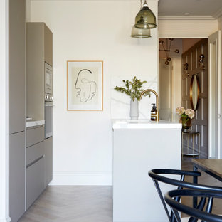 Design ideas for a contemporary galley kitchen in London with flat-panel cabinets, grey cabinets, stainless steel appliances, a breakfast bar, grey floors and white worktops.