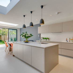 Large contemporary galley open plan kitchen in London with flat-panel cabinets, granite worktops, an island, white worktops, beige cabinets, beige floors, a submerged sink and beige splashback.