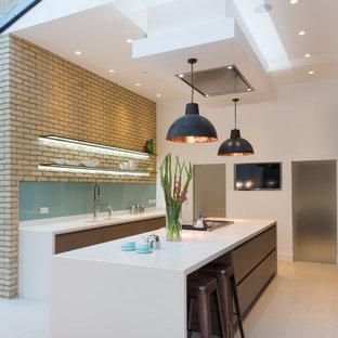 Inspiration for a large contemporary galley kitchen/diner in London with an integrated sink, flat-panel cabinets, medium wood cabinets, composite countertops, glass sheet splashback, integrated appliances, ceramic flooring and an island.