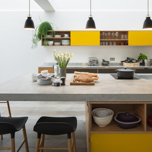 Photo of a contemporary galley kitchen in London with concrete worktops, an island, a double-bowl sink, flat-panel cabinets, yellow cabinets, grey floors, grey worktops and light hardwood flooring.