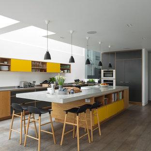 Cette image montre une grande cuisine minimaliste en L avec un plan de travail en béton, un électroménager en acier inoxydable, un îlot central, un placard à porte plane, des portes de placard jaunes, un sol en bois clair, un sol gris et un plan de travail gris.