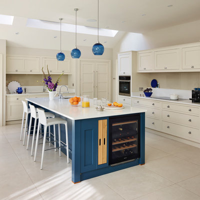Transitional beige floor kitchen photo in London with an undermount sink, shaker cabinets, beige cabinets, beige backsplash, glass sheet backsplash, paneled appliances and an island