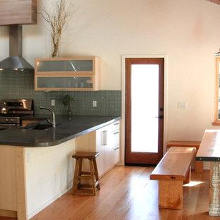 Ispirazione per una cucina moderna di medie dimensioni con lavello sottopiano, ante di vetro, ante in legno chiaro, top in cemento, paraspruzzi verde, paraspruzzi con piastrelle di vetro, elettrodomestici in acciaio inossidabile, parquet chiaro e penisola
