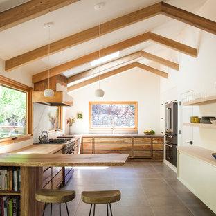 サンフランシスコのミッドセンチュリースタイルのおしゃれなペニンシュラキッチン (フラットパネル扉のキャビネット、中間色木目調キャビネット、大理石のキッチンパネル、カラー調理設備、セラミックタイルの床、白いキッチンパネル、茶色い床) の写真