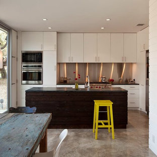 Eat-in kitchen - contemporary l-shaped concrete floor eat-in kitchen idea in Austin with flat-panel cabinets, white cabinets, metallic backsplash, stainless steel appliances and an island