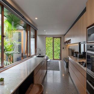 メルボルンの中くらいのコンテンポラリースタイルのおしゃれなキッチン (シングルシンク、フラットパネル扉のキャビネット、中間色木目調キャビネット、ミラータイルのキッチンパネル、パネルと同色の調理設備、グレーの床、ベージュのキッチンカウンター) の写真
