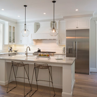Large transitional eat-in kitchen pictures - Eat-in kitchen - large transitional l-shaped medium tone wood floor eat-in kitchen idea in San Francisco with recessed-panel cabinets, white cabinets, stainless steel appliances and an island