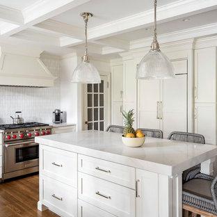 Geschlossene, Mittelgroße Klassische Küche in U-Form mit Unterbauwaschbecken, Schrankfronten im Shaker-Stil, gelben Schränken, Quarzwerkstein-Arbeitsplatte, Küchenrückwand in Weiß, Rückwand aus Mosaikfliesen, Elektrogeräten mit Frontblende, braunem Holzboden, Kücheninsel und weißer Arbeitsplatte in Boston
