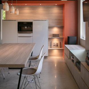 Foto di una cucina moderna di medie dimensioni con lavello sottopiano, ante lisce, ante gialle, top in quarzo composito, paraspruzzi arancione, paraspruzzi in lastra di pietra, elettrodomestici in acciaio inossidabile, pavimento in cemento e penisola