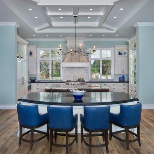 Maritime Wohnküche in U-Form mit profilierten Schrankfronten, weißen Schränken, Küchenrückwand in Weiß, Rückwand aus Mosaikfliesen, Elektrogeräten mit Frontblende, braunem Holzboden, zwei Kücheninseln und braunem Boden in Miami