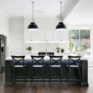 Inspiration for a large transitional l-shaped open plan kitchen in Sydney with shaker cabinets, black cabinets, tile benchtops, multi-coloured splashback, ceramic splashback, medium hardwood floors, with island, brown floor, a single-bowl sink, black appliances and white benchtop.