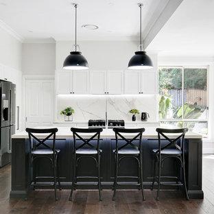 シドニーの大きいトランジショナルスタイルのおしゃれなキッチン (シェーカースタイル扉のキャビネット、黒いキャビネット、タイルカウンター、マルチカラーのキッチンパネル、セラミックタイルのキッチンパネル、無垢フローリング、茶色い床、シングルシンク、黒い調理設備、白いキッチンカウンター) の写真