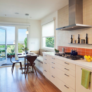 This is an example of a modern eat-in kitchen in San Francisco with flat-panel cabinets, beige cabinets and orange splashback.