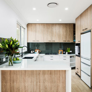 Inspiration for a scandinavian u-shaped kitchen in Sydney with an undermount sink, flat-panel cabinets, light wood cabinets, glass sheet splashback, white appliances, light hardwood floors, a peninsula, beige floor and white benchtop.