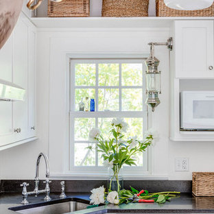 Small shabby-chic style u-shaped eat-in kitchen in Boston with an undermount sink, shaker cabinets, white cabinets, soapstone benchtops, white splashback, cement tile splashback, stainless steel appliances, medium hardwood floors, a peninsula and brown floor.