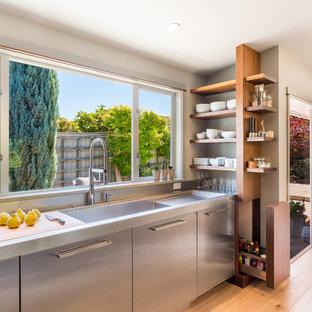 Moderne Küche mit flächenbündigen Schrankfronten, Speckstein-Arbeitsplatte, integriertem Waschbecken, Edelstahlfronten und hellem Holzboden in Seattle