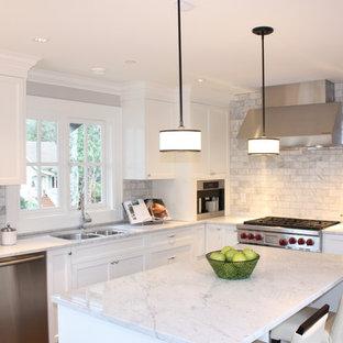 Klassische Küche mit Küchengeräten aus Edelstahl und Rückwand aus Marmor in Vancouver