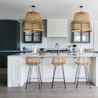 Inspiration for an expansive beach style open plan kitchen in London with glass-front cabinets, blue cabinets, stainless steel appliances, light hardwood flooring, an island, grey worktops and granite worktops.