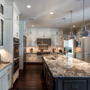 Inspiration for a large transitional l-shaped dark wood floor eat-in kitchen remodel in Houston with granite countertops, an undermount sink, raised-panel cabinets, white cabinets, white backsplash, ceramic backsplash, stainless steel appliances and an island