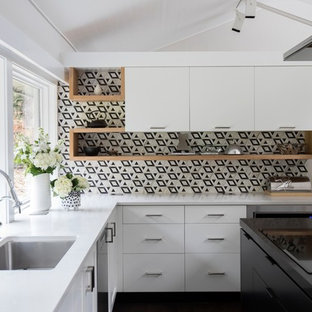 Inspiration for a large midcentury u-shaped kitchen in Vancouver with an undermount sink, quartz benchtops, black splashback, marble splashback, panelled appliances, dark hardwood floors, with island, brown floor, flat-panel cabinets, white cabinets and black benchtop.