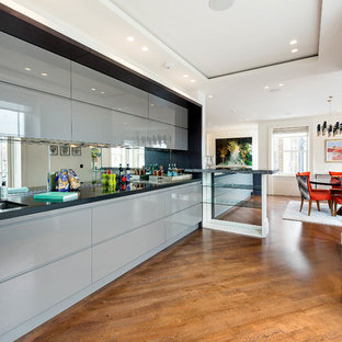 Contemporary single-wall kitchen in London with a double-bowl sink, flat-panel cabinets, blue cabinets, mirror splashback, medium hardwood flooring, brown floors and black worktops.