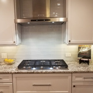 Mid-sized transitional dark wood floor and brown floor kitchen photo in Houston with an undermount sink, recessed-panel cabinets, white cabinets, granite countertops, white backsplash, glass tile backsplash and stainless steel appliances