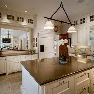 Große Klassische Küche mit Kassettenfronten, weißen Schränken, Küchenrückwand in Weiß, Elektrogeräten mit Frontblende, Travertin, Kücheninsel und braunem Boden in New York