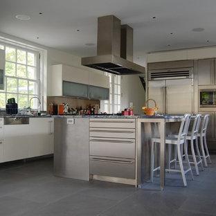 ニューヨークの大きいインダストリアルスタイルのおしゃれなキッチン (フラットパネル扉のキャビネット、ステンレスキャビネット、御影石カウンター、アンダーカウンターシンク、メタリックのキッチンパネル、メタルタイルのキッチンパネル、シルバーの調理設備の、コンクリートの床) の写真