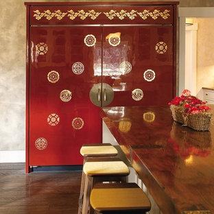ニューヨークの大きいアジアンスタイルのおしゃれなキッチン (エプロンフロントシンク、フラットパネル扉のキャビネット、赤いキャビネット、木材カウンター、パネルと同色の調理設備、無垢フローリング) の写真