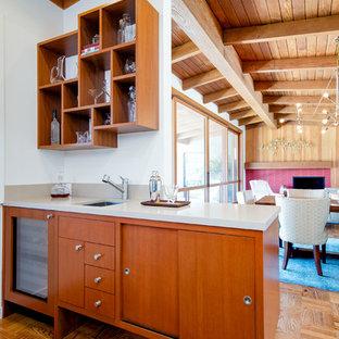 Foto på ett stort 50 tals grå kök, med en undermonterad diskho, släta luckor, skåp i mellenmörkt trä, bänkskiva i kvarts, blått stänkskydd, stänkskydd i keramik, rostfria vitvaror, ljust trägolv och en köksö