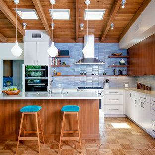 Large midcentury l-shaped open plan kitchen in Los Angeles with an undermount sink, flat-panel cabinets, medium wood cabinets, quartz benchtops, blue splashback, ceramic splashback, stainless steel appliances, light hardwood floors, with island and grey benchtop.