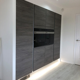 Design ideas for a medium sized contemporary l-shaped kitchen/diner in Glasgow with an integrated sink, flat-panel cabinets, grey cabinets, quartz worktops, brown splashback, wood splashback, stainless steel appliances, vinyl flooring, a breakfast bar, grey floors and grey worktops.