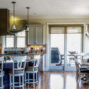 Geschlossene, Einzeilige, Mittelgroße Maritime Küche mit Schrankfronten mit vertiefter Füllung, dunklen Holzschränken, Granit-Arbeitsplatte, Kücheninsel, Küchenrückwand in Beige, Rückwand aus Porzellanfliesen, Elektrogeräten mit Frontblende, hellem Holzboden, beigem Boden und Triple-Waschtisch in Providence