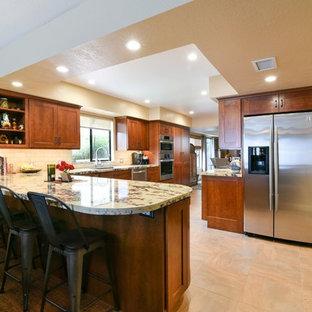 サンタバーバラの広いサンタフェスタイルのおしゃれなキッチン (アンダーカウンターシンク、シェーカースタイル扉のキャビネット、濃色木目調キャビネット、御影石カウンター、ベージュキッチンパネル、ガラスまたは窓のキッチンパネル、シルバーの調理設備、セラミックタイルの床、ベージュの床) の写真