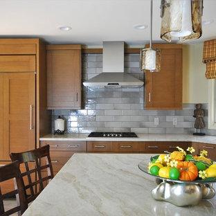 フィラデルフィアのアジアンスタイルのおしゃれなアイランドキッチン (アンダーカウンターシンク、シェーカースタイル扉のキャビネット、中間色木目調キャビネット、珪岩カウンター、グレーのキッチンパネル、サブウェイタイルのキッチンパネル、シルバーの調理設備、セラミックタイルの床、ベージュの床、ベージュのキッチンカウンター) の写真