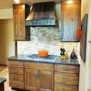 フェニックスの小さいサンタフェスタイルのおしゃれなキッチン (エプロンフロントシンク、シェーカースタイル扉のキャビネット、茶色いキャビネット、クオーツストーンカウンター、ベージュキッチンパネル、石タイルのキッチンパネル、シルバーの調理設備の、テラコッタタイルの床) の写真