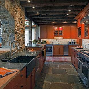 ボルチモアのエクレクティックスタイルのおしゃれなキッチン (シルバーの調理設備の、ソープストーンカウンター、一体型シンク、スレートの床、茶色いキャビネット) の写真