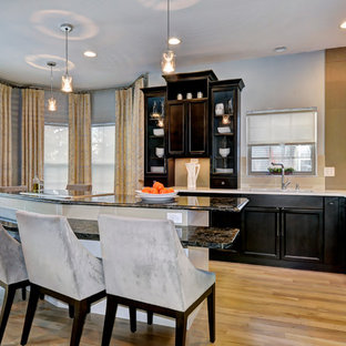 Photo of a transitional l-shaped eat-in kitchen in Columbus with louvered cabinets, quartz benchtops, stainless steel appliances, an undermount sink, dark wood cabinets and ceramic splashback.