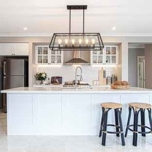 Large beach style galley kitchen pantry in Melbourne with a single-bowl sink, white cabinets, quartz benchtops, white splashback, ceramic splashback, stainless steel appliances, ceramic floors, with island, beige floor and white benchtop.